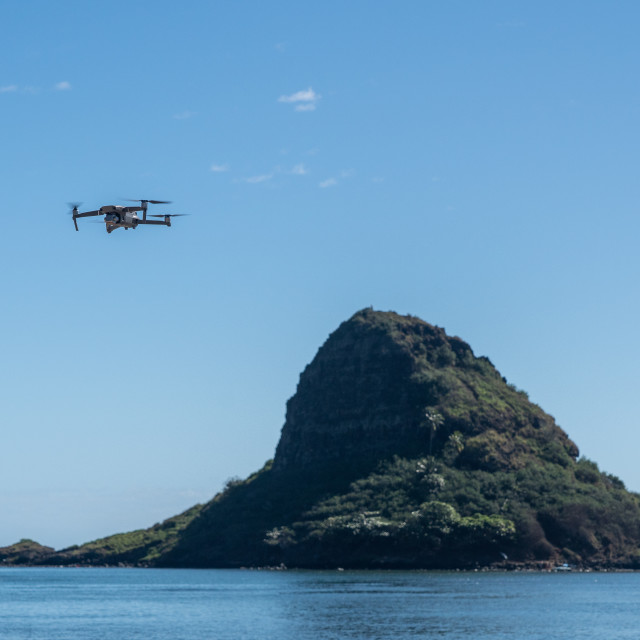 """""""Drone flying in front of the rock called Chinamans Hat or Mokolii"""" stock image"""