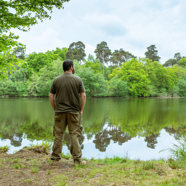 """Man standing next to a lake on an overcast spring day in England"" stock image"