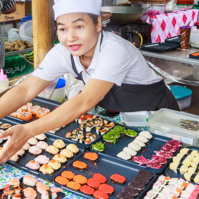 """A woman vendor serving sushi"" stock image"