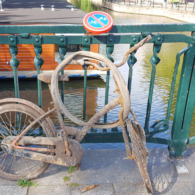 """An old rusty bike under No Bike Parking sign Amsterdam"" stock image"