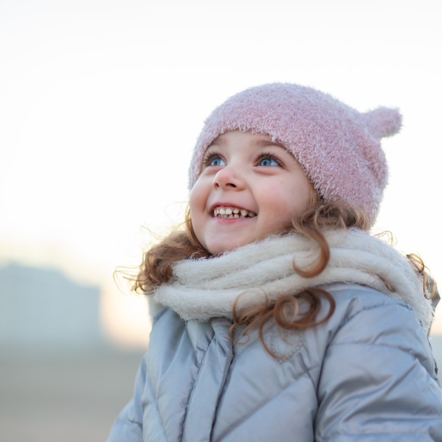 """Adorable little girl smiles and looks at the sky."" stock image"