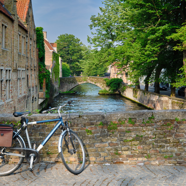 """Bicyccle on a bridge near canal and old houses. Bruges (Brugge), Belgium"" stock image"