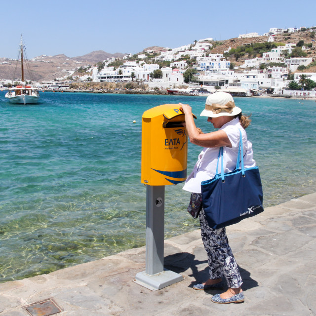 """Mykonos, Greece - July 23rd 2016: Woman posting a card in postbox by the..."" stock image"
