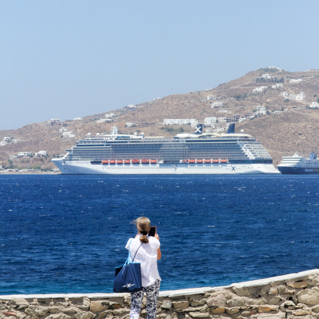 """Mykonos, Greece - July 23rd 2016: Woman taking a photo of a cruise ship. The..."" stock image"
