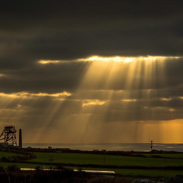 """Sun rays over Cornish tin mine"" stock image"