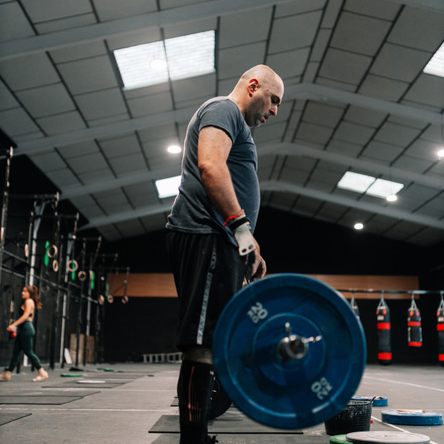 """Adult bald man weightlifter exercising in gym"" stock image"