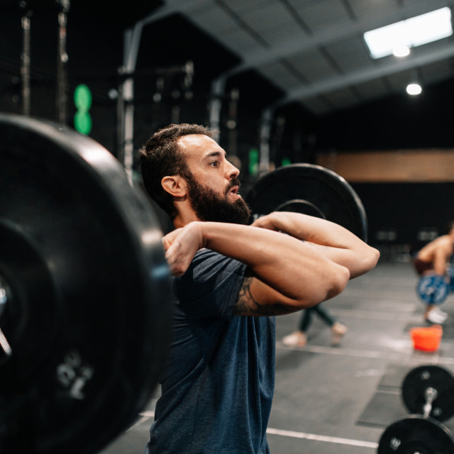 """Young male weightlifter exercising in gym"" stock image"