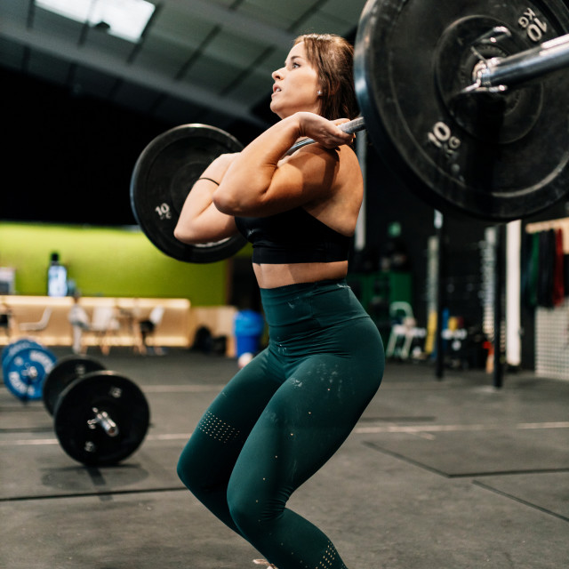 """Young female weightlifter exercising in gym"" stock image"
