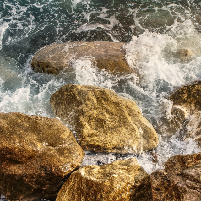 """Sea water swirling over rocks"" stock image"
