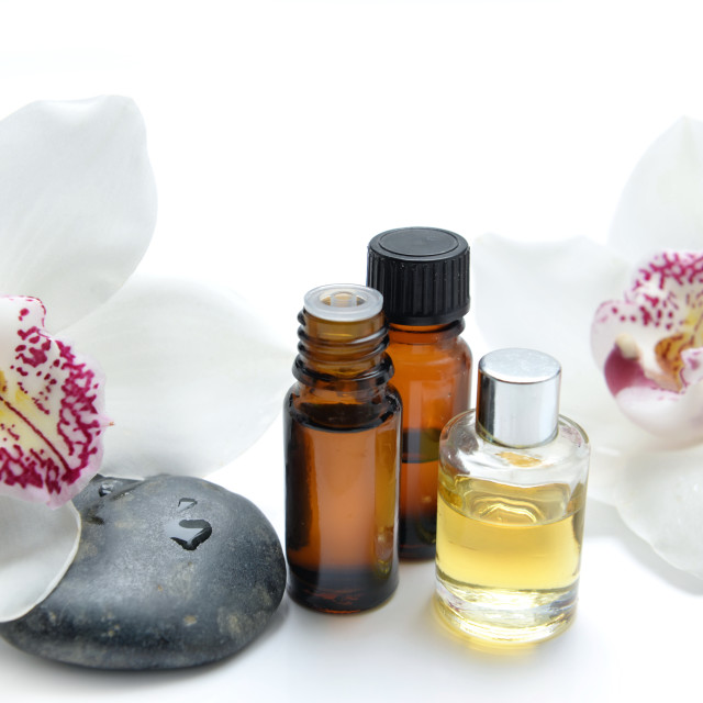 """oil bottles and pebbles with beautiful orchids on white background"" stock image"