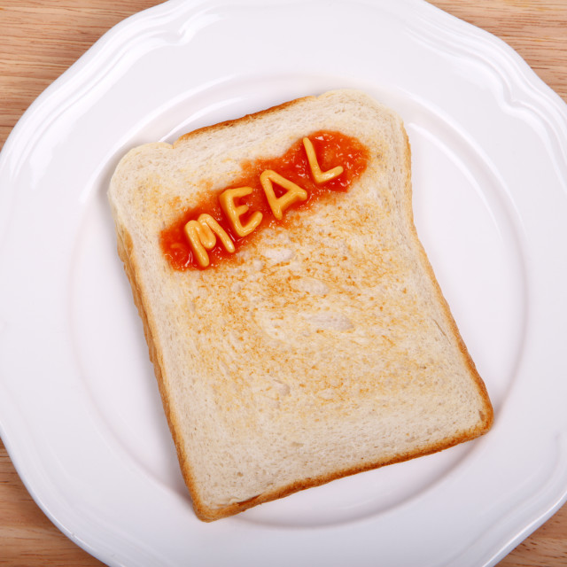 """A slice of toast on a plate with the word meal spelled out in alphabet spaghetti"" stock image"