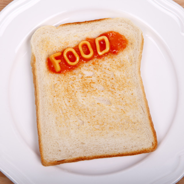"""The word food spelled out with alphabet spaghetti on a slice of toast"" stock image"