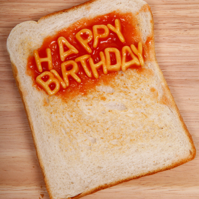 """The words Happy Birthday spelled out on a slice of toast with alphabet spaghetti"" stock image"