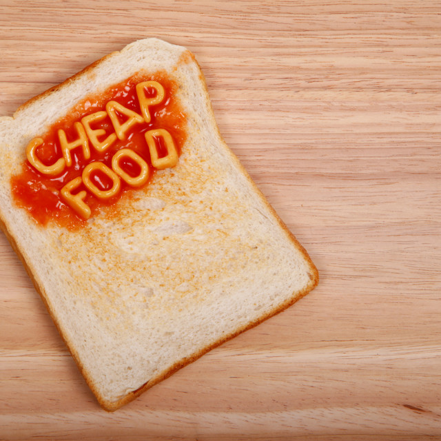 """The words cheap food spelled out on a piece of toast with alphabet spaghetti"" stock image"