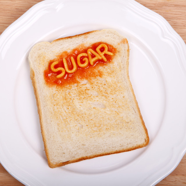 """The word sugar spelled out on a slice of toast with alphabet spaghetti"" stock image"