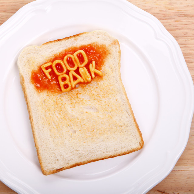 """The word food bank spelled out on a slice of toast with alphabet spaghetti"" stock image"