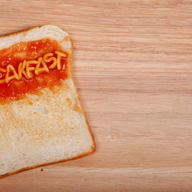 """The word breakfast spelled out on a slice of toast with alphabet spaghetti"" stock image"