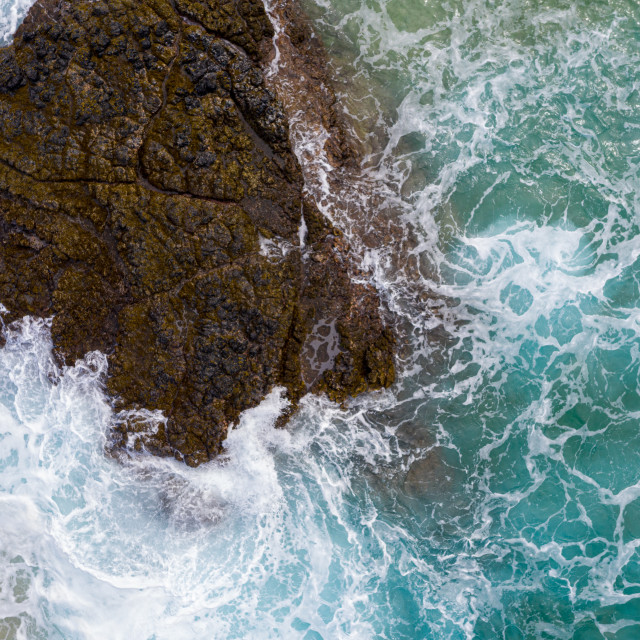 """Vertical top down view of waves crashing over rocks on Lumahai beach on Kauai"" stock image"