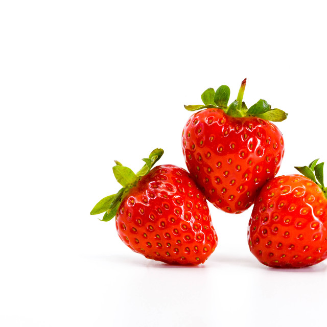 """Close up of three ripe strawberries balancing on each other. Space for copy right."" stock image"