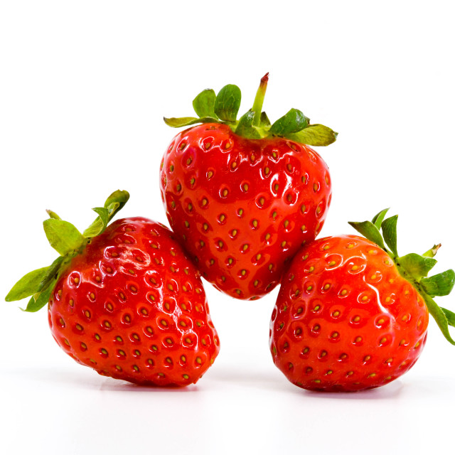 """Close up of three ripe strawberries balancing on each other."" stock image"