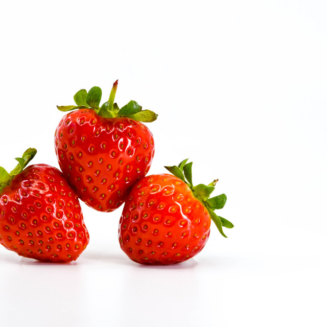 """Close up of three ripe strawberries balancing on each other. Space for copy left."" stock image"
