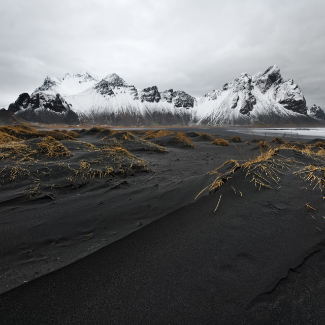 """Mountain range in front of black sand dunes"" stock image"