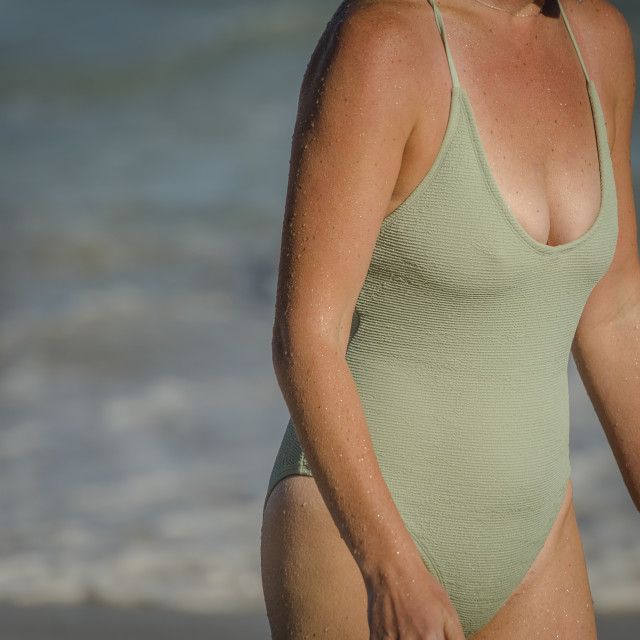 """""""Woman walkiing from the sea after a swim in the ocean."""" stock image"""