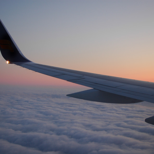 """Above the clouds sunset with plane wing"" stock image"