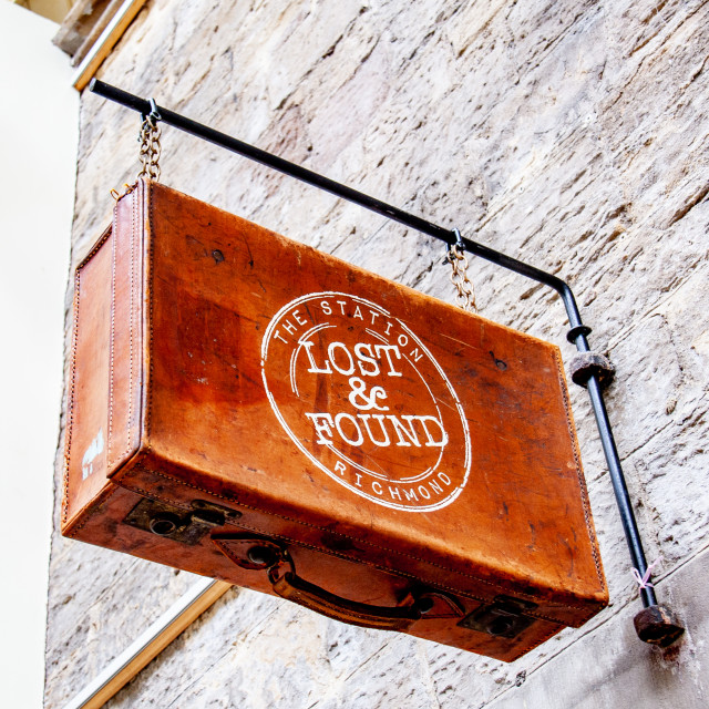 """Vintage Suitcase used as hanging Lost and Found Sign"" stock image"