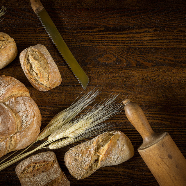 """Traditional fresh bread with a blade of wheat on a wooden backgr"" stock image"