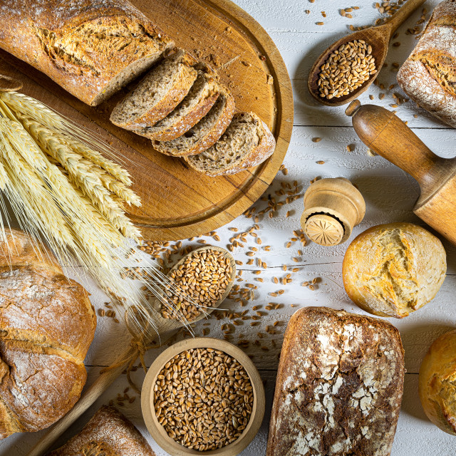 """Traditional wheat bread, rolls and ears of cereals on a white wo"" stock image"