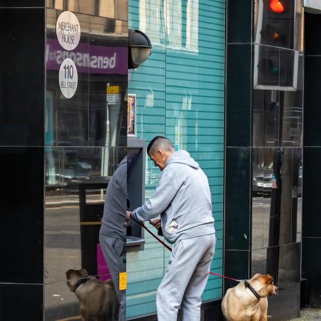 """Cashline Kid getting money at the bottom of High Street Glasgow"" stock image"
