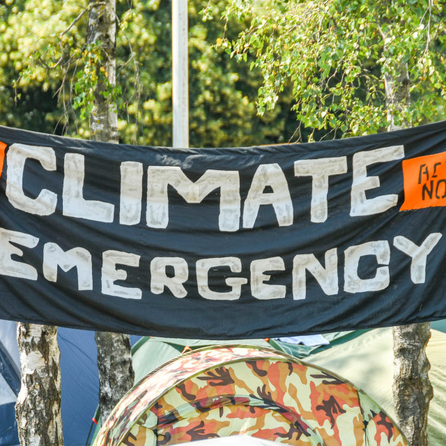 """""""""""Climate Emergency"""" banner hung between trees in a makeshift campsite"""" stock image"""