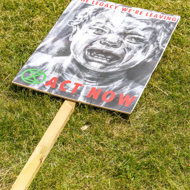 """""""""""Act Now"""" placard on wooden pole on the ground in Cardiff as part of protest by Extinction Rebellion."""" stock image"""