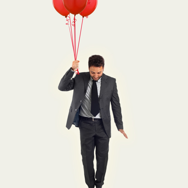 """Businessman flying with balloons on abstract background with copy space"" stock image"