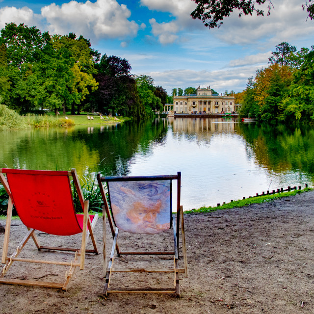 """Colourful deckchairs with view over lake to Palace on the Isle, Warsaw (Polands capital city)"" stock image"