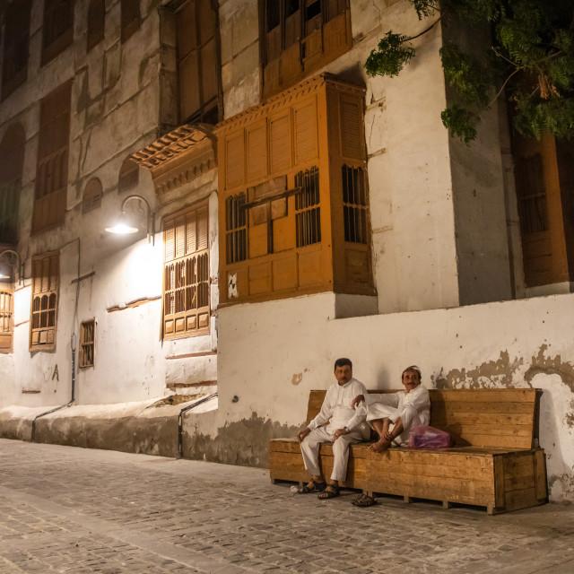 """Two men resting on a bench in al-Balad quarter, Mecca province, Jeddah, Saudi..."" stock image"
