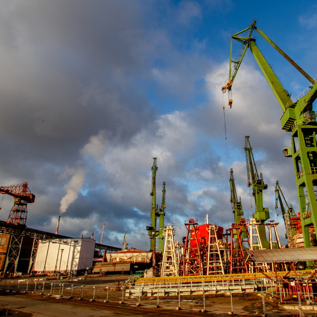 """Gdansk, Poland, Shipyard Cranes and Steelworks., Partially built ship in background."" stock image"