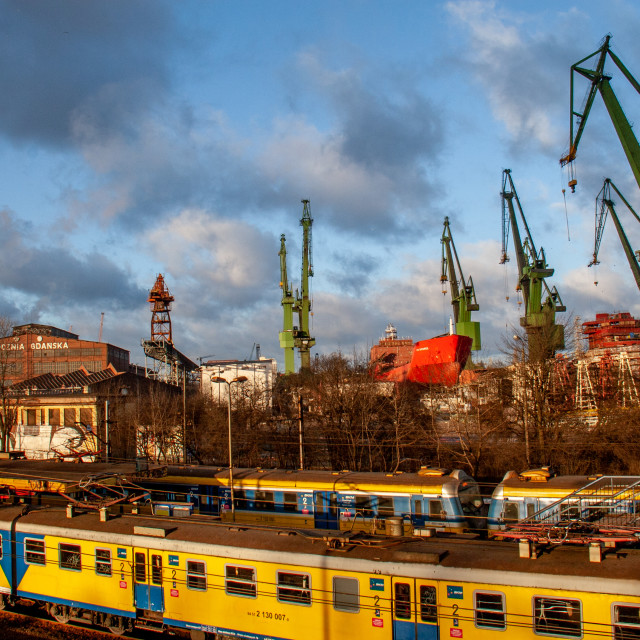 """Gdansk, Poland, Shipyard Cranes and Steelworks., Partially built ship in background and electric train carriages to foreground."" stock image"