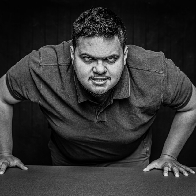 """Black and White Aggressive Latino Man Leans In"" stock image"