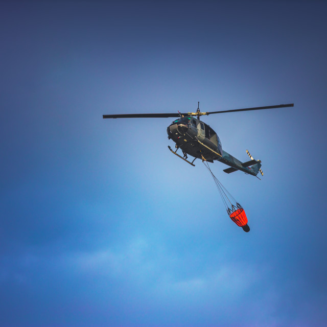 """Firefighter Helicopter Dropping Sea Water on a Fire over tropica"" stock image"
