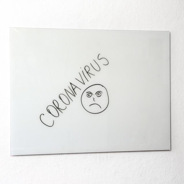"""Sad face and Coronavirus on white board"" stock image"