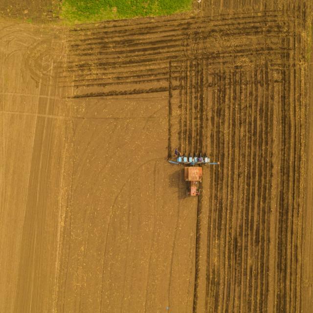 """Traktor working on spring field"" stock image"