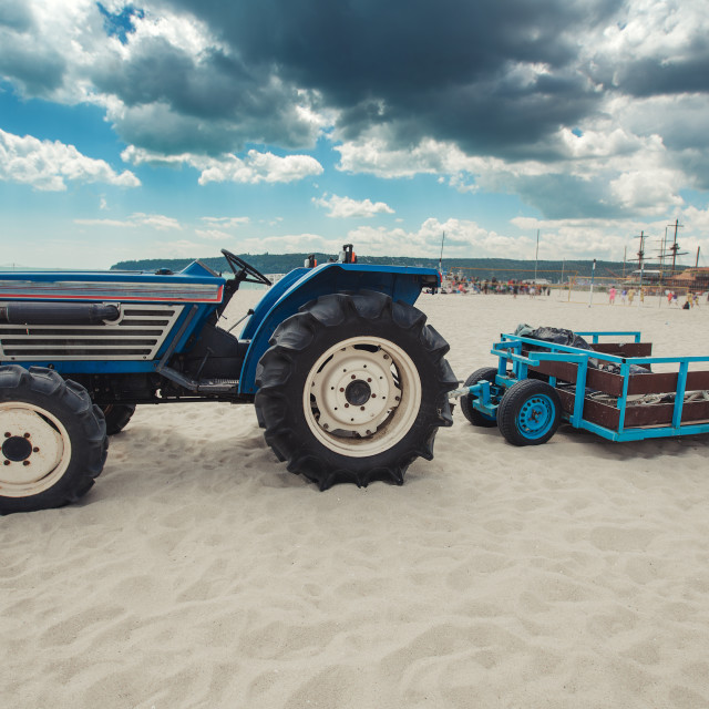 """Tractor machine with trailer cleaning rubbish on the beach"" stock image"