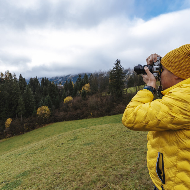 """""""Male traveller dressed in yellow jacket taking pictures of Alps with camera ..."""" stock image"""