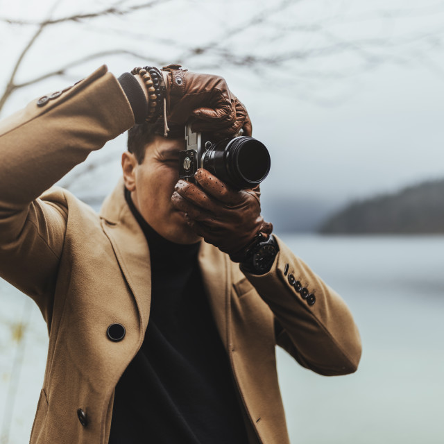 """Young male photographer in brown coat taking pictures with a small mirrorless..."" stock image"