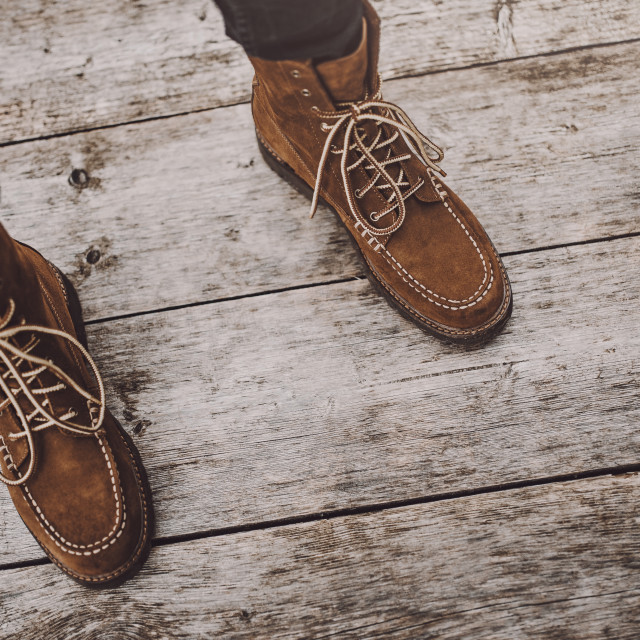 """Pair of stylish mens leather winter boots / Standing on an old wooden deck..."" stock image"