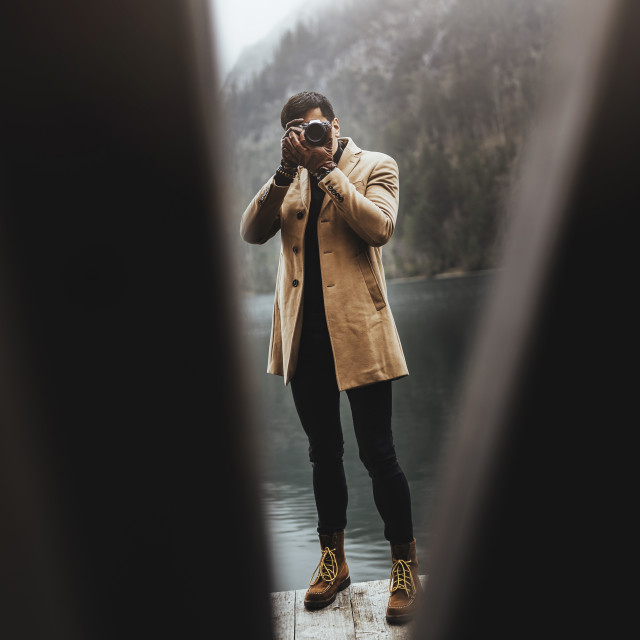 """Full body shot of young male photographer in brown coat taking pictures with..."" stock image"