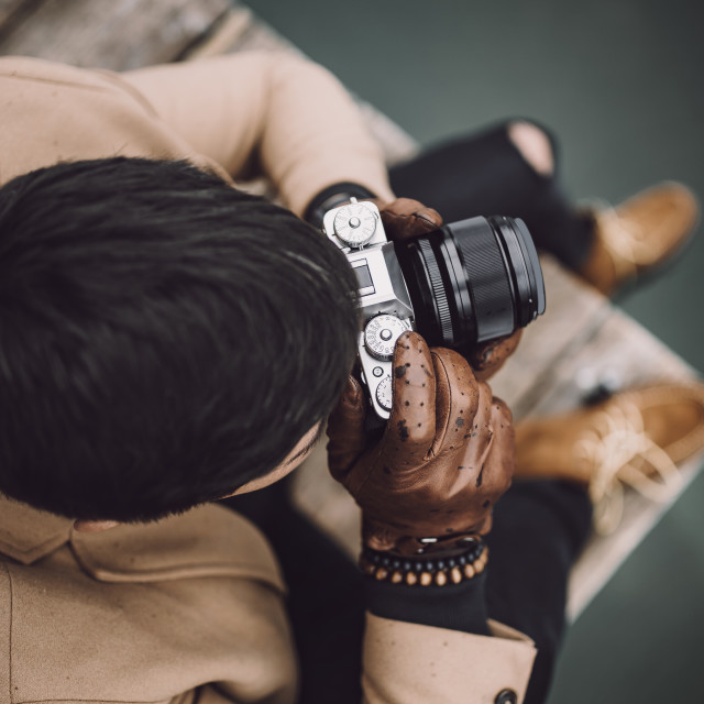 """Close-up shot of young male photographer in brown coat taking pictures with a..."" stock image"