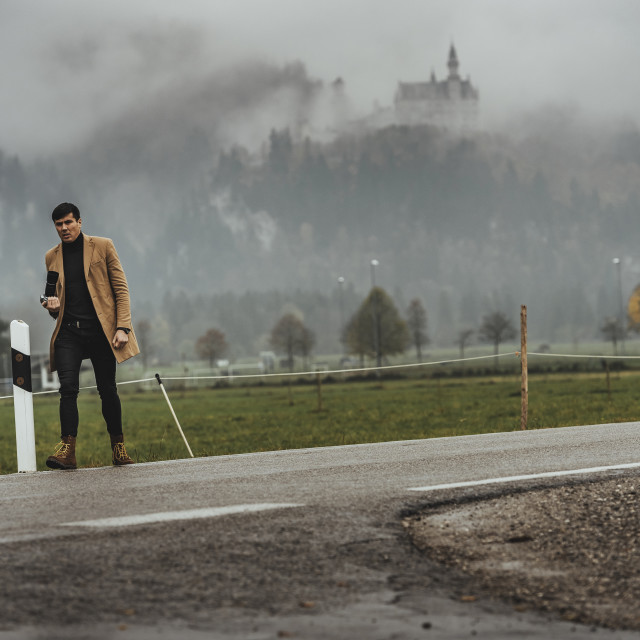 """Young male photographer in brown coat taking pictures of Neuschwanstein..."" stock image"